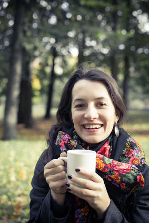 Girl in an autumn part with a white cup of hot drink Stock Photo - 17242107