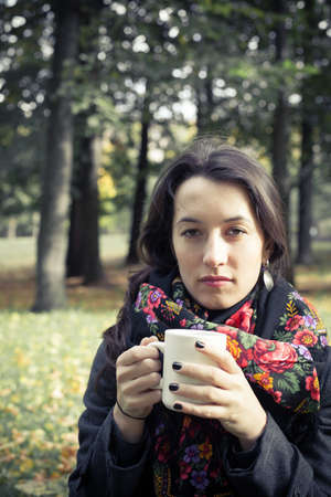 Girl in an autumn part with a white cup of hot drink Stock Photo - 17242109