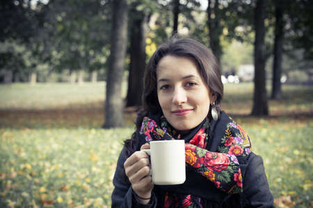 Girl in an autumn part with a white cup of hot drink Stock Photo - 17242106