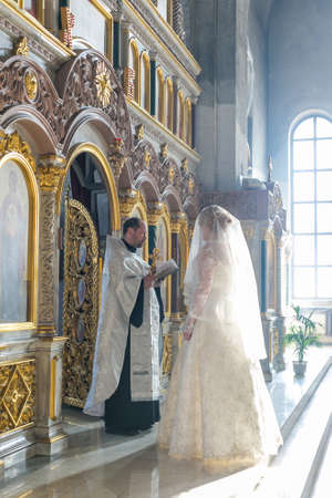 iconostasis: MOSCOW - MARCH 10: bride and groom stand opposite the priest near iconostasis in the rays of light during orthodox wedding ceremony on March 10, 2013 in Moscow