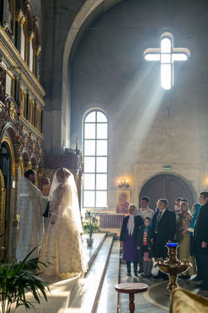 iconostasis: MOSCOW - MARCH 10: bride and groom stand opposite the iconostasis in the rays of light during orthodox wedding ceremony on March 10, 2013 in Moscow