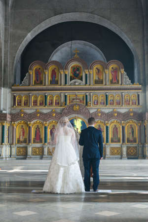 iconostasis: MOSCOW - MARCH 10: bride and groom stan behind the priest opposite the iconostasis during orthodox wedding ceremony on March 10, 2013 in Moscow Editorial