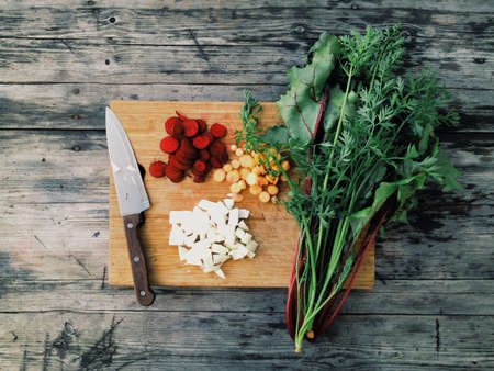 wood table: Wood table with a board with vegetables Stock Photo