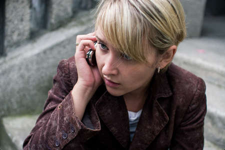 light brown eyes: Young blonde girl with fringe, dressed in velvet brown jacket, is talking on the phone, looking sideways Stock Photo