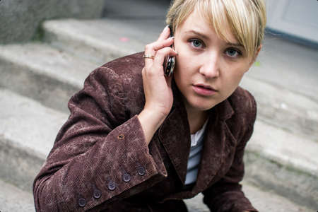 Girl with blonde fringe sitting on the steps and talking by phone