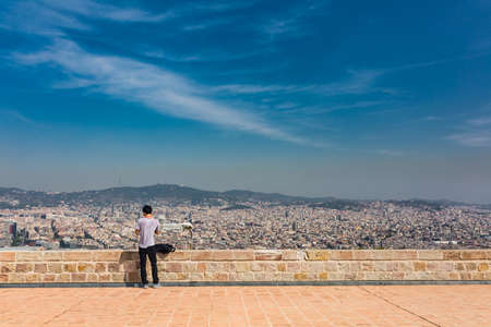 Beautiful city landscape in Barcelona and unidentified boy in summer time