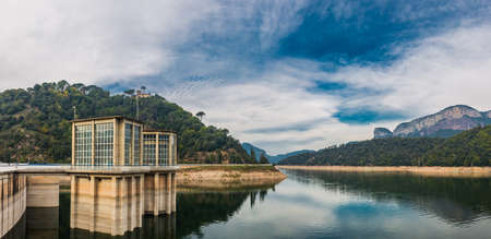 Beautiful nature landscape with dam building in vivid colors.