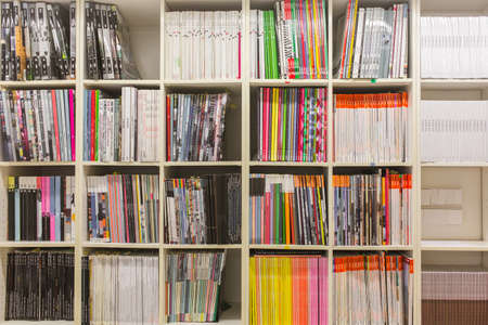 catalogs: BARCELONA, SPAIN - OCTOBER 7, 2015: Bookshelves with variety of different colorful books and magazines