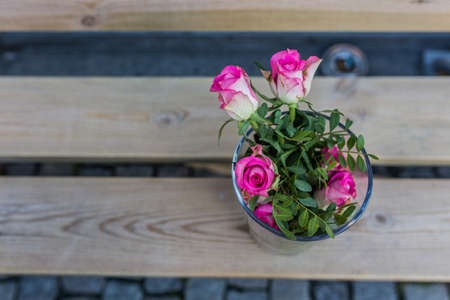 Beautiful pink bouquet flowers standing in vase on bench Stock Photo