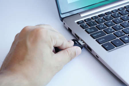 plugging: Hand plugging usb card reader to laptop Stock Photo