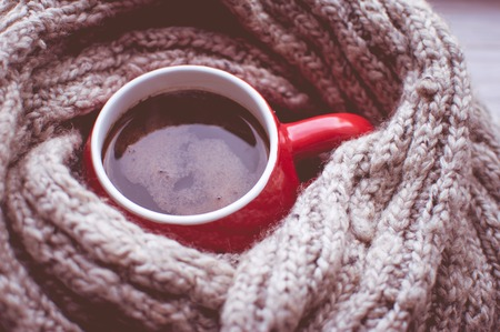 Cup of coffee wrapped in a woolen scarf. Concept autumn. Concept winter