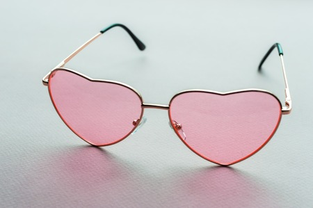 rose-colored glasses in the shape of a heart close-up. concept love. feast day of the holy valentine. The 14th of February.