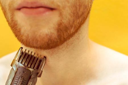 Close-up of a man shaving his beard with shaving machine Reklamní fotografie