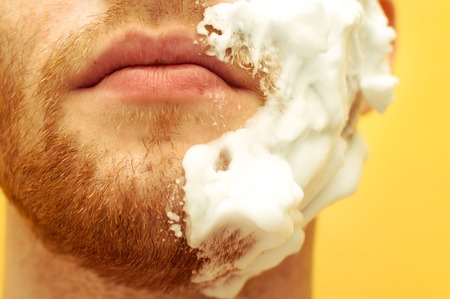 Young man with a shaving foam on his face half. Close-up of a beard