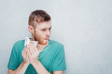 Young man sneezes into a paper napkin. Concept winter and flu