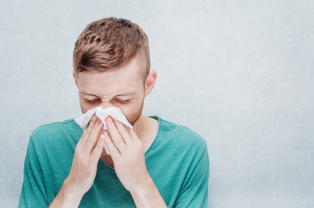 Young guy is sick with the flu. Concept of cold and runny nose. Stock Photo