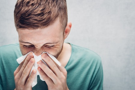Young guy is blowing in a paper napkin. Concept of disease. Season colds and flu. Imagens