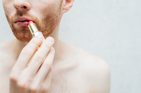 young man paints his lips with lipstick. Close-up. Stock Photo - 111442439