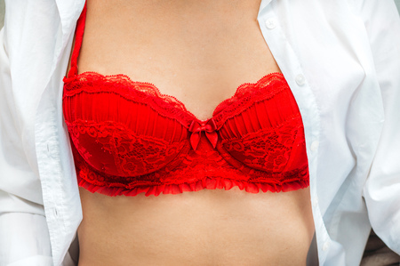 woman in an unbuttoned white shirt and red bra. Close up of female breast