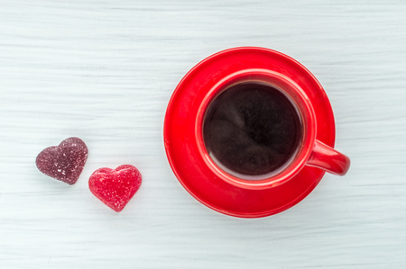 Cup of coffee in a red cup and two hearts on a white background. Greeting card