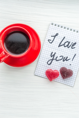 Cup of coffee, a candy in the shape of a heart and a note I love you. Vertical photo