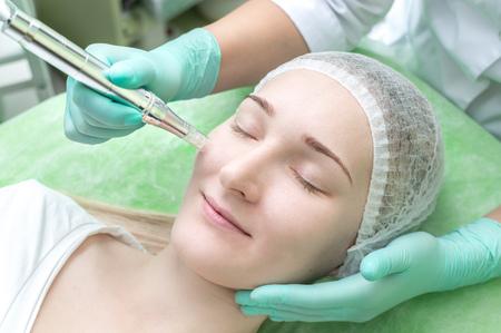 Kosmetikerin, die einem jungen Mädchen im Schönheitssalon Mesopilling macht, Nahaufnahme