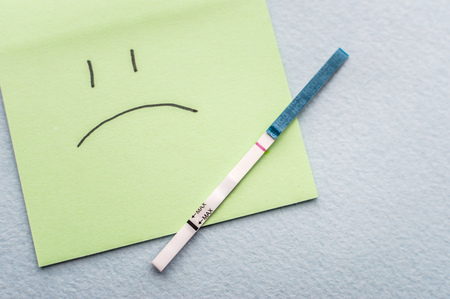 One-strip pregnancy test and sad smile. Infertility concept