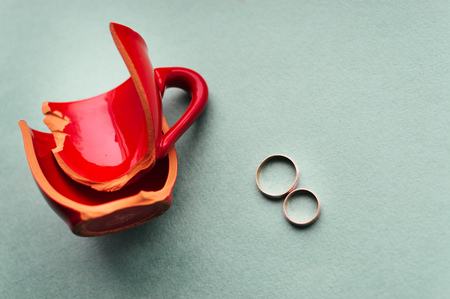Broken red cup and wedding rings. Concept parting