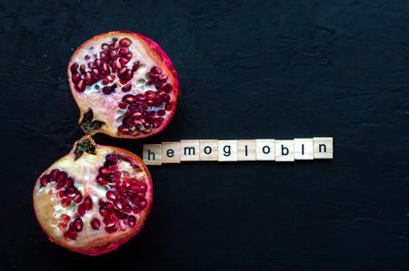 Cut pomegranate on a black background. Concept hemoglobin