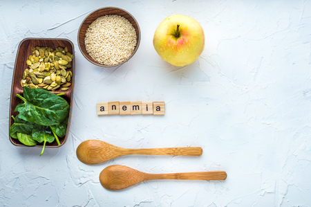 Spinach, pumpkin seeds, sesame, apple and two wooden spoons on a white background. Anemia concept. Close-up.