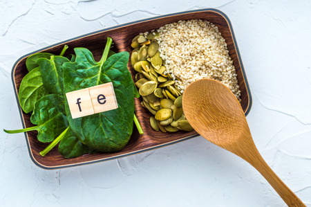 Spinach, pumpkin seeds, sesame and one wood spoon on a white background. microelement FE. Close-up.