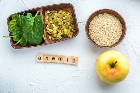 Spinach, pumpkin seeds, sesame, apple on a white background. Trace element FE. Close-up.