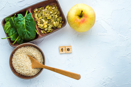 Spinach, pumpkin seeds, sesame, apple and one wood spoon on a white background. microelement FE. Close-up.