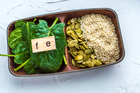 Spinach, pumpkin seeds, sesame on a white background. microelement FE. Close-up.