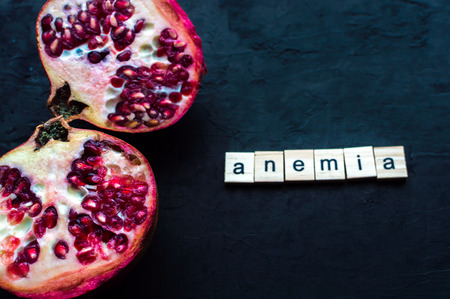 Cut pomegranate on a black background. Concept anemia Stock Photo