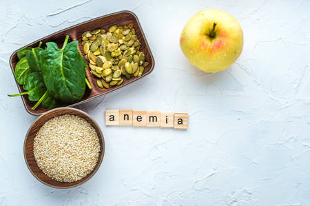 Spinach, pumpkin seeds, sesame, apple on a white background. Anemia concept. Close-up Stock Photo