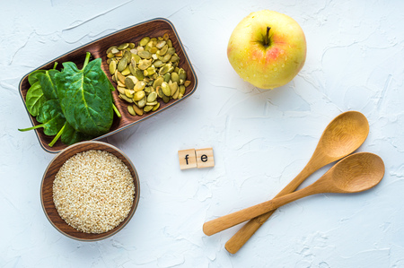 Spinach, pumpkin seeds, sesame, apple and two wood spoon on a white background. microelement FE. Close-up. Stock Photo