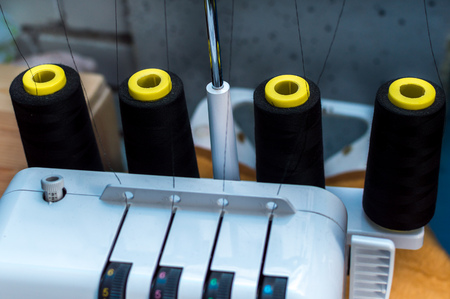 Machine overlock closeup with black spools of thread. Concept sewing