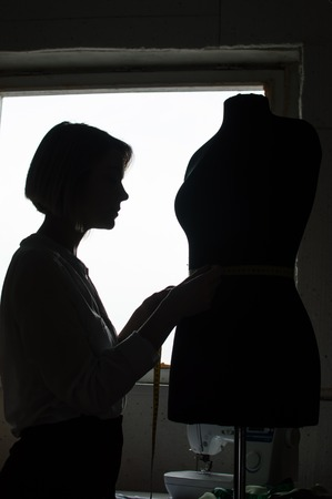 Silhouette of a designer and mannequin for clothes. Concept designer, tailoring, seamstress, tailor, fashion designer. Foto de archivo