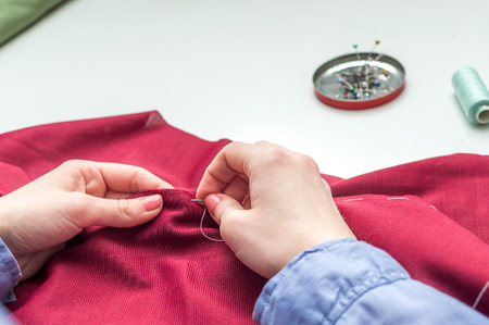 Seamstress sews clothes by hand. Woman's hands. Close-up. Handcraft concept.