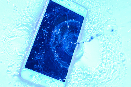 Phone in water close up. Concept broken phone. Copy space