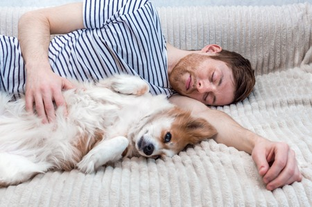 Portrait of a young man sleeping with his dog in an embrace on the bed 版權商用圖片 - 121168681