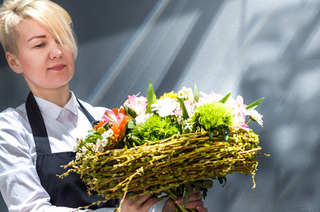 Young woman florist in the sun in a flower shop close-up holds a bouquet of flowers.
