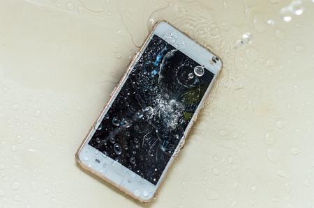 Phone in the water. Concept broken phone. Smartphone repair concept Stok Fotoğraf