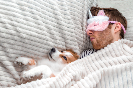 Closeup portrait of a young man in a pink mask sleeping in a bed under a rug with his dog