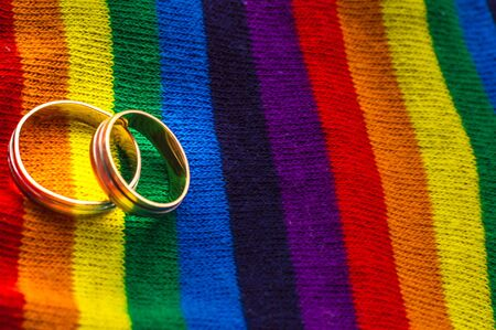 Two wedding rings on the fabric colors of the rainbow. Concept same-sex marriage. Cope space