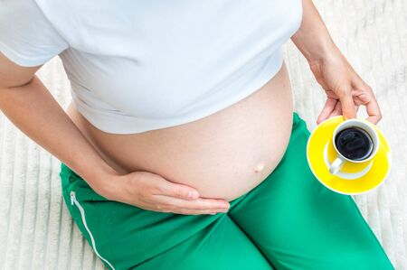 pregnant woman holds in her hand a cup of coffee. Close-up. Caffeine concept during pregnancy