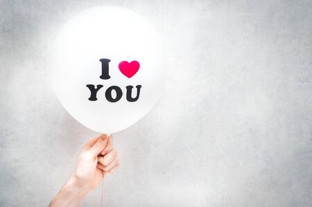 inscription I love you on a white balloon in the hand of a man. Valentines Day