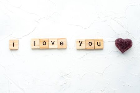 inscription I love you is laid out in wooden letters on a white wooden background. Valentines day concept. February.