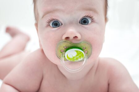 Close-up portrait of baby with pacifier in mouth